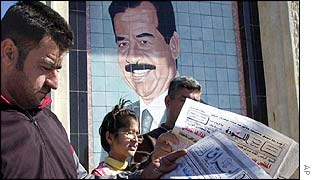 Iraqi reading a newspaper in front of a portrait of Saddam Hussein