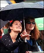 Women sit in the rain at Wimbledon