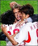 South Korea coach Guus Hiddink is hugged by his players