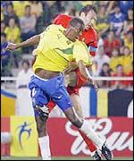 Marc Wilmots rises above Roque Junior during Belgium's match against Brazil