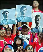 South Korea fans hold aloft posters of Guus Hiddink
