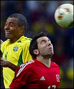 Turkey's Muzzy Izzet and Brazil's Gilberto Silva fight for the ball