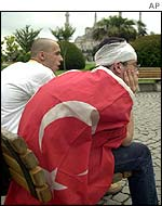 Dejected fans sit in a square in Istanbul
