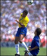 Cafu heads the ball away under pressure from Roberto Baggio during the 1994 World Cup final