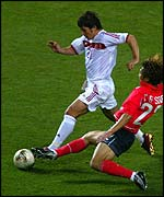 Turkey's Emre Belozoglu escapes the tackle of South Korea's Chong Gug-Song