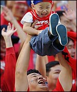 A South Korean fan lifts his son into the air during the  defeat by Turkey