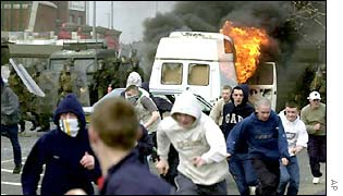 Youths run away from a burning van during a Belfast riot