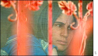 Palestinian woman peers through a screen on an open window as Israeli soldiers question her male family members