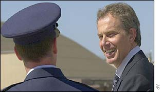 Tony Blair is greeted by a US military officer