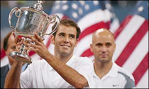 Pete Sampras holds the trophy aloft as Andre Agassi looks on