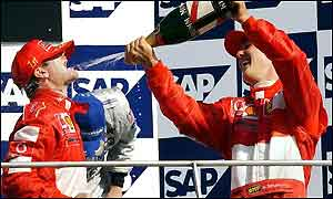 Brazils Rubens Barrrichello, left, gets a drink of champagne from Michael Schumacher