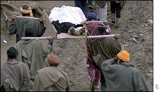 Villagers carry bodies of victims of an attack on Sikhs in March 2000