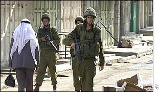Israeli soldiers walk past an old Palestinian man in the occupied West Bank city of Hebron