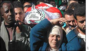 Amina Zaki Sabbagh carries the body of her son Ala Sabbagh during his funeral  in Jenin