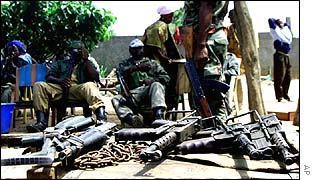 Rebel soldiers with a pile of weapons in Ivory Coast
