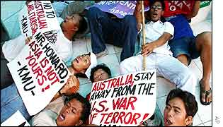 Protesters shout slogans as they stage a die-in on the steps of the closed Australian embassy in Manila