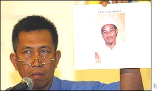 Chief investigator Pastika holds up a picture of Mukhlas