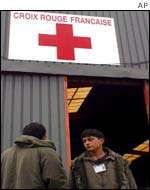 Refugees stand by the entrance to the Red Cross centre in Sangatte