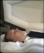 Paul Kenyon lying in a coffin