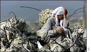 Woman sits in the rubble of her home in Jenin