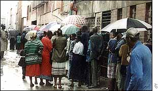 Zimbabweans queue for food outside a store in Harare