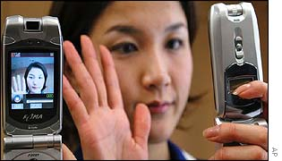 An employee of NTT DoCoMo demonstrates a 3G phone