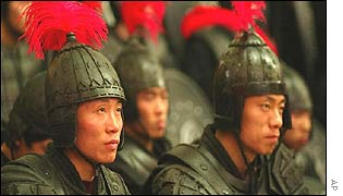 Extras dressed as warriors sit through a press conference about Chinese director Zhang Yimou's epic, Hero
