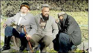 Muslim men from China's far west Xinjiang province's Uighurs minority, sit outside the Pakistan embassy in Beijing 12 November 2002, waiting for their visa applications to be processed