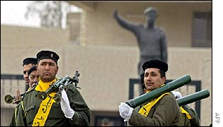 Iraqi soldiers parade in front of Saddam statue in Baghdad