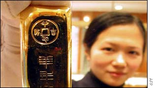 A shop assistant holds up a gold bar