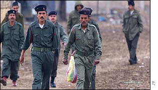 Iraqi soldiers walk to a military camp as UN weapons inspectors enter a base