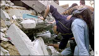 Palestinians search through rubble of blown up building