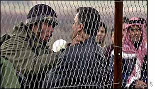 An Israeli soldier stops a Palestinian behind a fence