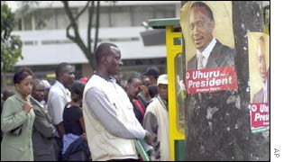 Nairobi residents stand next to a Kanu election poster