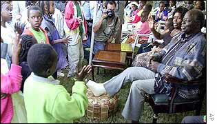 Mwai Kibaki listens to orphaned children sing during a Christmas Eve service