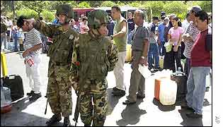 Venezuelan soldiers patrol a Caracas petrol station as customers queue