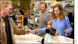 Store owner Larry Trogdon (centre) in his shop where the winning ticket was bought