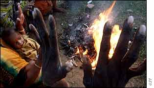 Homeless Bangladeshis gather around a small fire in search of warmth in Dhaka