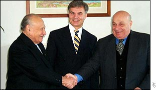Rauf Denktash and Glafcos Clerides shake hands as a UN envoy watches, Jan 2002
