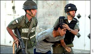 Israeli soldiers detain a Palestinian