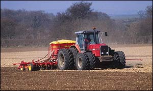 Farmer sowing seeds with tractor