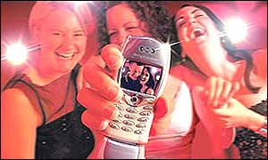 Girls holding out new picture messaging phone