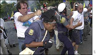 An opposition protester hits a policeman during clashes