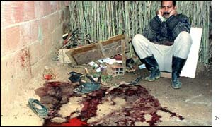 An unidentified relative looks at a pool of blood