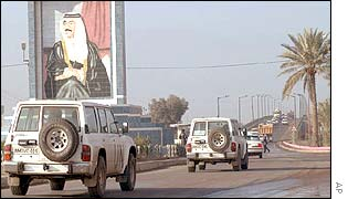 Convoy of UN weapons inspectors pass a portrait of Saddam Hussein