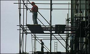 Construction workers erect scaffolding