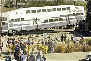 Commuters from a Metrolink train are escorted away from the scene by emergency workers