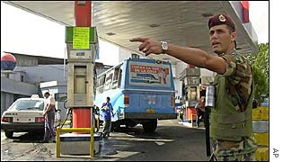 Soldier directs cars at petrol station in Caracas