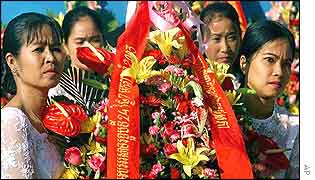 Cambodian women carry a wreath at a ceremony commemorating the 24th anniversary of the ouster of the Khmer  Rouge
