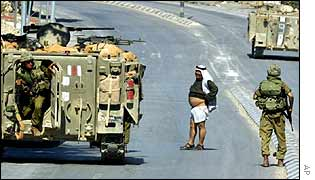 Israeli troops check Palestinian for secreted bombs